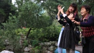 Stock Video Footage of Mother showing her daughter how to take photos with smart phone in Shanghai park