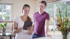 4K Happy young man & woman chatting at home & looking at computer tablet - stock footage