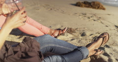 Two black womens feet wearing sandals in the sand of the beach sitting in chairs Stock Footage