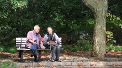 Two asian senior men talking while sitting on bench at People's square park Stock Footage