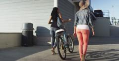 Two black women friends walking bike under the pier at beach on sunny day Stock Footage