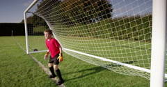 A young goal keeper fails to save a goal during a match in a soccer field. Stock Footage