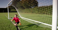 A young goal keeper fails to save a goal during a match in a soccer field. Arkistovideo