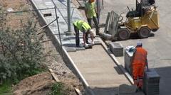 Skilled builders team lay tiles sidewalk pavement. 4K Stock Footage