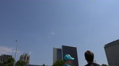 Father teach young boy to fly kite high in sky between skyscraper. 4K Stock Footage