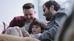 Same sex couple family on the couch watching digital tablet Stock Footage