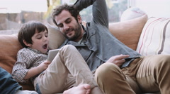 Same sex couple family on the couch playing with digital tablet and smart phone Stock Footage