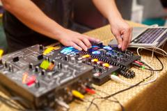 DJ mixing music on console at the night club Stock Photos