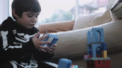 Stock Video Footage of Little boy dressed up for Halloween playing with building blocks