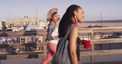 Black woman pointing out towards the ocean while wlaking with best friend on Stock Footage