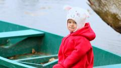 Beautiful smiling child sitting in wooden boat on river. Little girl portrait Arkistovideo