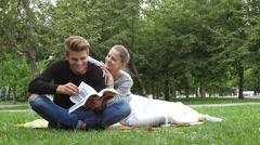 Couple students sitting on the grass and laughing. slow motion Stock Footage