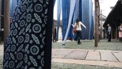 Tourists taking photos around dyed fabric pieces hanging to dry and swaying Stock Footage