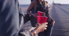 Close up of red plastic cups being held by two women friends leaning against Stock Footage