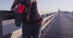 Woman leaning against wooden railing of pier while holding red plastic cup Stock Footage