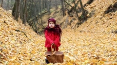 Cute little girl standing in autumn wood. Child holding basket for picnic Stock Footage