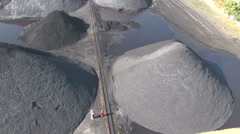 Workers walk between heaps of coal Stock Footage