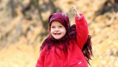 Child cheerfully throwing orange autumn leaves up - stock footage