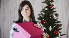 Festive beautiful young woman unwrapping Christmas gift - stock footage