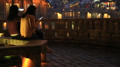 Young asian women sitting on the bench watching the night view of water town Stock Footage