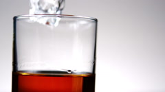 Ice falling into tumbler of whiskey and ice Stock Footage