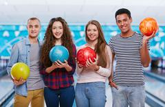 Group of four friends in a bowling alley Stock Photos