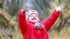 Close up of child cheerfully throwing orange autumn leaves up - stock footage