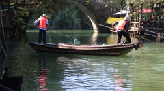 Workers on a boat picking up leaves from the river for cleaning in Wuzhen Stock Footage