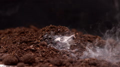 Firecracker under soil against black background Stock Footage