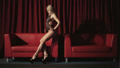 Woman dancing in strip club on a red sofa - stock footage