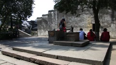Chinese tourists sitting and resting on the stairs around common well Stock Footage