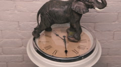 Figure of elephant standing on a rotating clock - stock footage