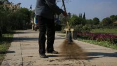 Chinese male worker cleaning a road around the purple flowerfields Stock Footage