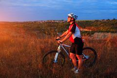 young adult cyclist riding mountain bike in the countryside - stock photo