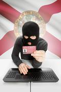 Hacker with ID card in hand and USA states flag on background - Florida - stock photo