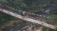 People walking across bridge, Pokhara, Nepal. Stock Footage