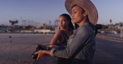 Black women best friends laughing and talking while looking out over ocean - stock footage