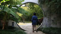 Aisain woman walking through the round gate of the beautiful oriental garden Stock Footage