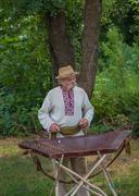 Grandpa in Ukrainian costume playing the dulcimer Stock Photos