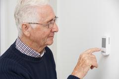 Smiling Senior Man Adjusting Central Heating Thermostat - stock photo