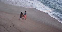 High angle view of black women best friends walking along sandy shore Stock Footage