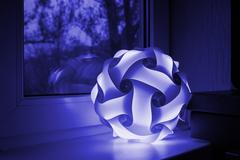 Included lamp in blue background near window Stock Photos