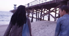 Two happy black young women walking under pier at sunset Stock Footage