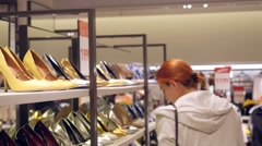 Stock Video Footage of Young red-haired woman choosing shoes in a shoe store