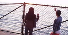 Two women leaning against chain link fence waching sun set over the ocean Stock Footage