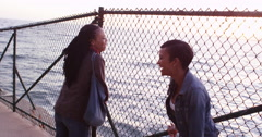 Two black women friends talking and laughing as they look though chain link - stock footage