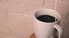 Stock Video Footage of Add milk in the coffee. Glass turns on the stand.