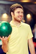 Stock Photo of happy young man holding ball in bowling club
