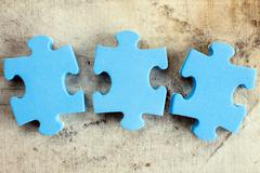 Three puzzle pieces on old canvas - stock photo