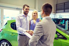 Happy couple with car dealer in auto show or salon Stock Photos
